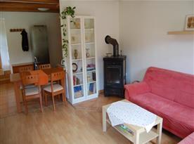 Obývací pokoj se sedačkou, krbovými kamny a jídelním koutem