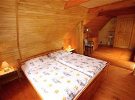 Podkrovní ložnice s lůžky, nočním stolkem, lampičkou a umyvadlem