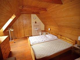 Podkrovní ložnice s lůžky a umyvadlem