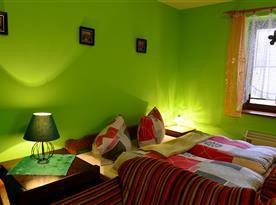 Obývací pokoj s lůžky, sedací soupravou a televizí