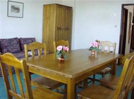 Pokoj B se stolem,  židlemi, rozkládacím gaučem a skříní