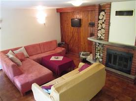Společenská místnost se sedací soupravou, krbem a televizí