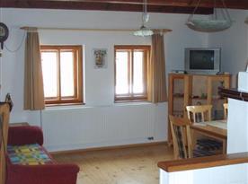 Společenská místnost s gaučem, jídelním stolem, židlemi a televizí