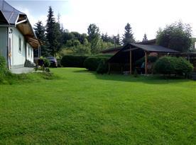 Pohled ze zahrady na venkovní posezení a chalupu