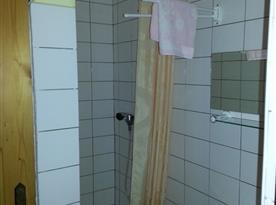 Sociální zařízení se sprchovým koutem, umyvadlem a zrcadlem